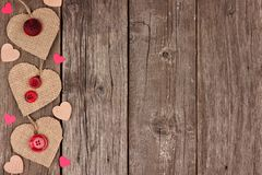 Side border of Valentines Day burlap hearts over rustic wood. Side border of Valentines Day burlap hearts with buttons and confetti over a rustic wooden Royalty Free Stock Photo