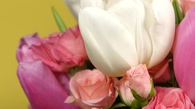 Side of bouquet flower with roses and tulips, on yellow, rotation, close up stock video footage