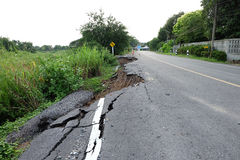 Side of the broken asphalt road collapsed and fallen after flood Royalty Free Stock Image