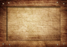 Side of brown wooden crate, box, wall or frame with screws.  Royalty Free Stock Photos