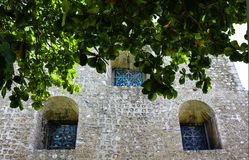 Side of cathederal with deepset arched stainedglass windows with tropical foliage stock image