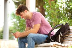 Side of cheerful man sitting on park bench with backpack and cellphone Stock Photography