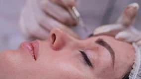 Side, close-up, of a girl who is on the procedure of permanent makeup. 4K Slow Mo. Side, close-up, of a girl who is on the procedure of permanent makeup stock footage