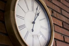 Side Close–up Of A Wooden Wall Clock With Roman Numerals Hanging In A Red Brick Wall. Stock Photos