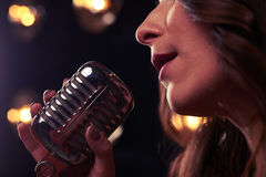 Side close-up of silver retro microphone in spotlights royalty free stock photo