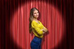 Side close-up of young woman in yellow jumper and blue jeans lit up by limelight standing with arms folded and looking stock photography