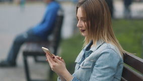 Side closeup of the beatiful young attractive model girl sitting on the bench near shopping mall and performing a selfie. Urban background stock video footage