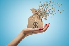 Free Side Closeup Of Woman`s Hand Facing Up And Holding Canvas Money Bag That Is Dissolving In Pieces On Light Blue Royalty Free Stock Photos - 168998298