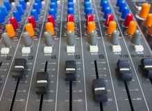Side closeup on a sliders of a mixing console. Stock Photos