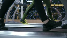 Side closeup view of a feet of a unrecognizable sportpeople in motion walking on treadmills in the gym warming up before. Training. Slowmotion shot stock footage