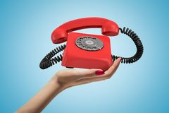 Side closeup of woman`s hand facing up and holding ringing retro phone on light blue background. Customer support. Communication devices. Keeping in touch stock photo