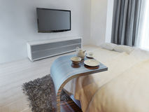 Side coffee table beside the bed in Contemporary style. Stock Photography