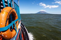 Side of colorful ferry boat with orange life preserver ring speeding along in lake to Volcano Royalty Free Stock Photography