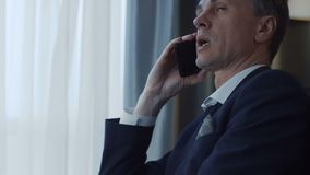 Adult businessman using phone and laptop. Side crop view of confident adult man in suit sitting at table in hotel room working on laptop and having business call stock video footage