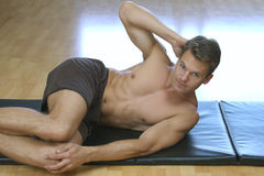 Side crunch sit up. Male athlete performs side crunch sit up on mat Stock Photography