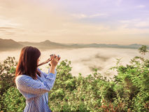 Side of cute young girl & x28;25s to 35s& x29; with her camera enjoy see a. Nd take picture to haze around mountain with sunrise and nice sky from north east Stock Image