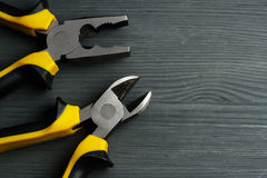Side cutters and combination pliers on a dark wooden background. Royalty Free Stock Photos