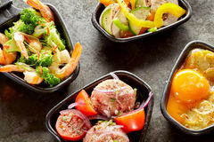 Side dishes of accompaniments for raclette. With colorful sliced fresh sweet peppers, prawn tails in broccoli, meatballs, and yellow egg yolk to be added to the Royalty Free Stock Image