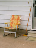By the side door. Old-style patio chair and broom by the side door royalty free stock image