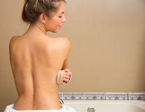 Side Dry Brush. Bare back of young woman holding dry brush to her side stock image