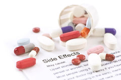 Side Effects. Assorted pills and capsules with side effects information sheet Royalty Free Stock Photo