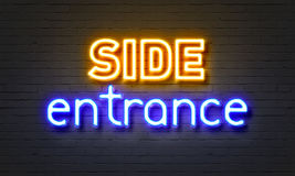 Side entrance neon sign on brick wall background. Stock Photography
