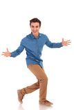 Side of an excited casual man inviting and walking. On white background Royalty Free Stock Image
