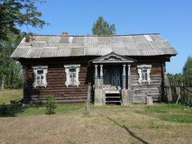 The side façade of a village house. With a porch and a sloping meadow stock photo