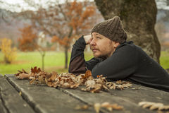 Side face close up portrait dreamer man with wool hat sitting on Royalty Free Stock Images