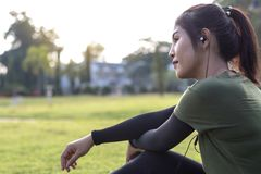 Side face of a young woman sitting in a park. royalty free stock image