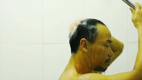 The side faces of Asian men Wet water from the shower and hand washing hair within the bathroom. The side faces of Asian men Wet water from the shower and hand stock video