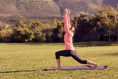 Side of a fit senior woman outdoors in yoga pose Royalty Free Stock Photos
