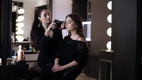 Side footage of young pretty girl in black during the makeup process with airbrush. Beautiful brunette female artist. Makes perfect surface skin for a model stock footage