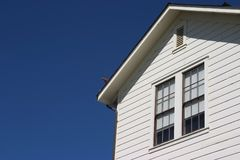 Side of Generic House. The side of a very iconic looking house presents itself against the sky stock photo