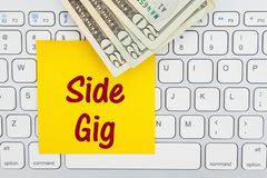 Side gig message with money on a keyboard with sticky note. Side gig message with money money on a computer keyboard with sticky note for your making money royalty free stock photography
