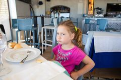 Side of girl eating and looking at with angry expression in rest. Side of four years old blonde little girl with pink eating bread, looking at with angry royalty free stock photos