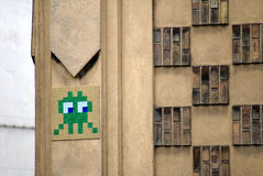 Side glance of a curious space invader mosaic. Fun realization of the famous 'invader' french artist on a wall of Paris. The space invader mosaic is having an Royalty Free Stock Photo