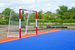 Side of goal and soccer field. Side of red and white goal and blue and orange soccer field Royalty Free Stock Photography