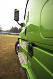 Side of green modern rig semi truck in perspective Stock Image