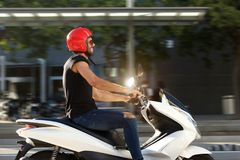 Side of handsome smiling man on motorcycle ride in city Royalty Free Stock Photo