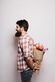 Side Handsome young man with beard  and nice bouquet of flowersSide Handsome young man with beard  and nice bouquet of flowers Stock Image
