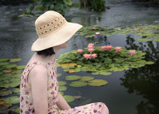 Side hat. Woman in straw hat in front of pond with pink water lilies Stock Photo