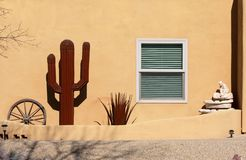 Side of a house with wagon wheel and metal cactus stock image