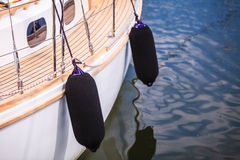 Side of hull sailboat with black fenders Royalty Free Stock Photo