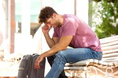 Side of laughing man sitting on park bench with luggage and cellphone Royalty Free Stock Photo
