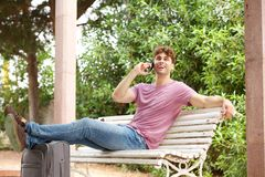 Side of laughing man sitting on park bench with suitcase and cellphone Royalty Free Stock Photos