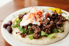 Side look at Gyro plate. Lamb gyro, Mediterranean style, topped with lettuce, tomato, and a special yogurt sauce royalty free stock images