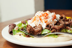 Side look at Gyro plate. Lamb gyro, Mediterranean style, topped with lettuce, tomato, and a special yogurt sauce royalty free stock photos