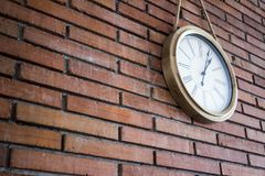 Side medium shot of a wooden wall clock with roman numerals hanging in a red brick wall. royalty free stock photo
