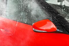 Side mirror of bright red car washed in self serve carwash, water spraying on the glass royalty free stock image
